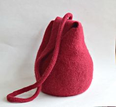 Simple, pear shaped felted purse with an integral strap. Pull the strap in one direction to open the purse. Pull it the opposite direction, and the purse closes. The bag is knit in the round from the bottom up, then felted in a washing machine. The I-cord straps are trimmed after felting, and the ends sewn together. Optional grommet where the strap pulls through the purse.