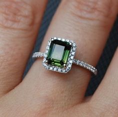 A green square cut stone with surrounding diamonds, lovely.