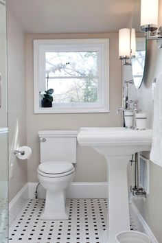 Neutral walls allow the white fixtures to pop in this transitional bathroom. A black and white tile floor adds a retro vibe to the space.