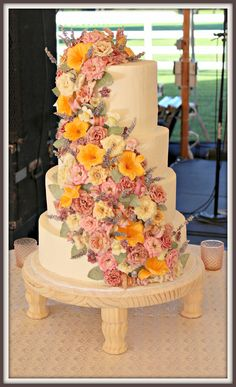 4 tiered wedding cake with alternating lace design.  Cascading organic edible flowers by Crystallized Flowers.  www.acakedream.com