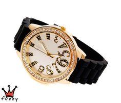 Γυναικείο ρολόι, στολισμένο με στρας περιμετρικά και  νούμερα με ιδιαίτερο σχήμα  σε μαύρο-χρυσό στο εσωτερικό του.  Λουράκι σε μαύρο χρώμα από σιλικόνη. Διάμετρος καντράν 45 mm.