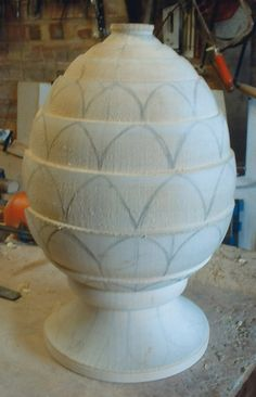The basic design is sketched on the shaped wood - pineapple design, wood shape, sketching, ornament, casting for stone