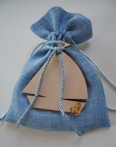 Blue pouch for boy's baptism decorated with a wooden boat in natural color and a gold mettalic anchor.
