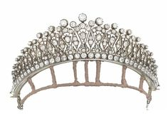 A LATE 19TH CENTURY DIAMOND TIARA   Designed as a series of graduated old-cut diamond fan shaped motifs, interspersed with similarly-set lozenge panels, with foliate and scroll detailing and diamond single-stone finials, raised on an old-cut diamond square collet line border, mounted in silver and gold, circa 1890, 4.0cm high, with later back chain for wearing as a necklace, leather tiara case