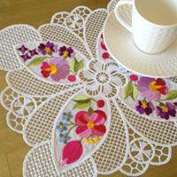 Classic white free standing lace makes a striking contrast to the colorful blossoms of Tea Doily Emma from Embroidery Necessity.
