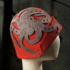 A classic 1920's cloche in dark red and adorned with giant octopus on the right temple. The folded back brim is dark red and top-stitched in alternating contrasting colors. The Kraken is various shades of gray with silk details.  You can order this hat in any color you like. There is no upcharge for a color change.  ***ALL HATS ARE MADE TO ORDER SO PLEASE SEND ME YOUR HEAD MEASUREMENT WHEN YOU PLACE YOUR ORDER***  All of my hats are hand felted Merino wool from non- tail docked sheep.  The…