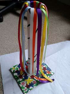 Beltane altar fairy-sized maypole I made. The actual pole is a ring from the middle of paper towels, hot-glued onto a piece of card and painted. I then hot glued ribbons into the top.