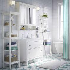 Ein weißes Badezimmer mit HEMNES Waschbeckenschrank mit 2 Schubladen, HEMNES Spiegelschrank mit 2 Türen und HEMNES Regal in Weiß und blauem Duschvorhang