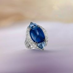 Mesmerizing ring featuring an exceptional sugarloaf Kashmir sapphire surrounded by rondelle diamonds and two heart shaped sapphires.