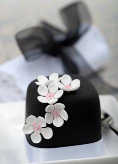 White blossoms on black mini cake.
