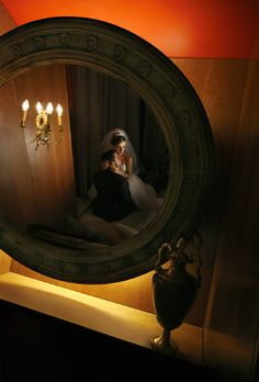 Bride in elbow length veil sits on groom - wedding photo by Jerry Ghionis