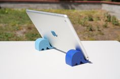 These two baby elephant stands hold almost all tablets. Use these stands to Skype or FaceTime with friends and family or to keep your tablet on one place at your desk. Two stands are needed to hold your tablet. We have several colors, so choose your combination! Get $5 off when you buy 2 stands: HOLIDAYGIFT Get $10 off when you buy 3 stands: 3HOLIDAYPRESENTS  Check out our other stands. We have Elephant, Whale, Cat, Dog, Dinosaur, Bird and Mustache stands! https://www.etsy.com/...