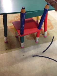 """ADORABLE WOOD DESK SET FOR A CHILD. THE LEGS OF THE TABLE AND CHAIR ARE STYLIZED INTO PENCILS WITH RUBBER ERASER ENDS. PAINTED IN PRIMARY COLORS OF BLUE, GREEN, RED AND YELLOW. CHAIR MEASURES 21"""" TALL, TABLE MEASURES 24"""" LONG BY 16"""" WIDE AND 17"""" TALL"""