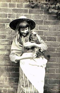 Victorian photograph of a young woman holding a cat, ca. 1890.