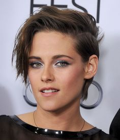 Kristen Stewart hit the red carpet in a metallic blue smoky eye illuminated with a glint of platinum pigment on the inner corners; rimming of black liner, while her sideswept boyish crop and bright pink blush blended toward the hairline.