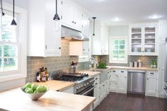 Nice take on a white kitchen - Nicole Curtis Design bathroom | Designer Gray tile, light fixtures, butcher block counters...