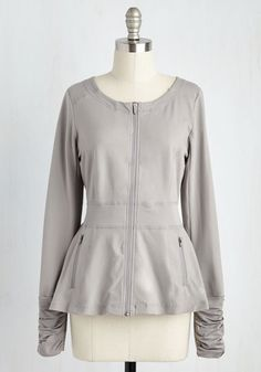 The best way to make a morning jog feel like a fast-paced runway is with this light grey jacket! An expert blend of stylish and sporty, this layer boasts thumb holes beneath its ruched sleeves, zippered side pockets, and an A-line fit that goes the distance for making you look as great as you feel.