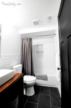 herringbone tile in inset and subway tile from shower carried up to ceiling and behind toilet and vanity