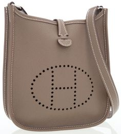 d6e39a27e441 The exterior of this beloved Hermes Evelyne miniature crossbody bag is done  in Etoupe Epsom leather