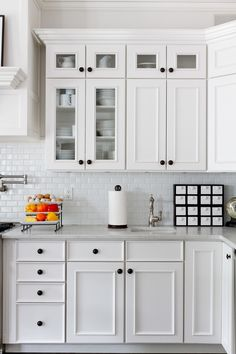 small subway tile in Kitchen Traditional with black cabinet hardware all white kitchen