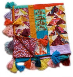I am in love with this Flying Geese quilt! The colors are energizing. I now want to bind my quilt with tassels!