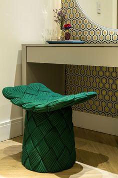 Decoração de apartamento moderno e cinza. No banheiro, lavabo, com revestimento, papel de parede, espelho redondo com iluminação indireta, banco verde e flores para decorar.
