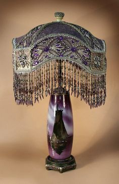 Vintage lamp covered in purple and silver metallic silk with beaded laces. Painted glass base. Exquisite!