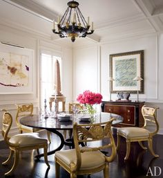 Surrounding the dining room table are regency-style gilt-wood chairs, cushioned with Hermès leather | archdigest.com