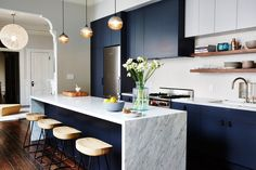 """If you ask Lambie, navy makes an exceptional base color for just about any room. """"We often use dark navy as a neutral base because it can be a beautiful complement to other warmer tones, particularly wood, brass, and brick,"""" she says. Plus, it can help """"bring out the blues of otherwise ordinary gray-tone marbles."""""""