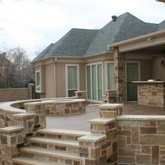 A wonderful place to spend a night outdoors, this custom patio includes an outdoor kitchen and fire pit. Stained concrete is used for the flooring part of the patio with complementing stone on the retaining walls, steps, kitchen and fire feature. Patio Builders, Curved Patio, Flagstone Patio, Concrete Patio, Backyard Patio, Wooden Greenhouses, Basic Kitchen, Outdoor Kitchen Design, Outdoor Living