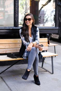 Kat Tanita of With Love From Kat wears a plaid button down, fur vest, grey skinny jeans, and black booties in NYC.