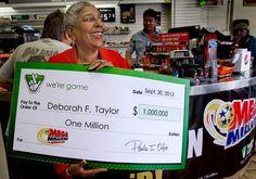 Virginia Lottery winner Deborah Taylor is presented with a check for $1 million Mega Millions dollars at Race Coast Mart in Hampton. (Joe Fudge / September 30, 2013)