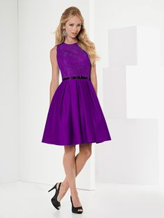 15034 - A pretty, short dress shown in cadburys purple. The skirt is satin with a lace bodice, dress detail is complete with dainty black belt around the waist.