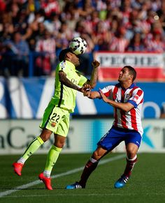 Daniel Alves of Barcelona battles for the ball with Koke of Atletico Madrid during the La Liga match between Club Atletico de Madrid and FC Barcelona at Vicente Calderon Stadium on May 17, 2015 in Madrid, Spain.