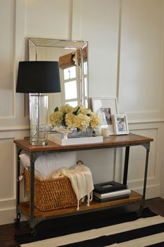 white walls, table, basket and blanket under, mirror, lamp, picture frames, greenery