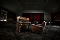 Un pianoforte abbandonato in una sala di ricevimento di un vecchio sanatorio.
