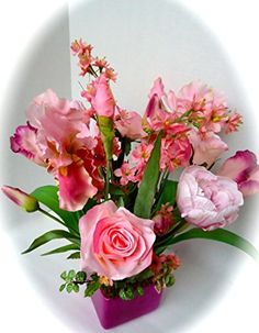 Floral Table Centerpiece-Pink Floral Centerpiece. This eye catching pink floral table arrangement is guaranteed to give you spring fever ! This floral centerpiece is filled with a variety of pink blooms including roses, tulips, cosmos, and iris. This arrangement would be perfect for a table centerpiece or on an end table in your home to welcome the beauty of the spring season. Simplistic yet bountiful in blooms you are sure to receive compliments from family and friends. The arrangement…
