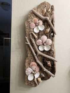 Beautiful decorative driftwood and shells wall art sculpture. This one-of-a-kind ocean themed wall decor is beautifully decorated driftwood with gorgeous shells accented with netting to created a wonderful masterpiece! Has hook for hanging. This large dri