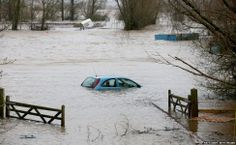 A car sits in flood water besides agricultural buildings on the Somerset Levels near Burrowbridge