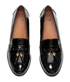 Black. Loafers in imitation patent leather with a tab and decorative tassels at front. Imitation leather lining and insoles and rubber soles. Heel height 1