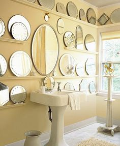 Chair rails are used to display a collection of mirrors in this bathroom. {via martha stewart living}