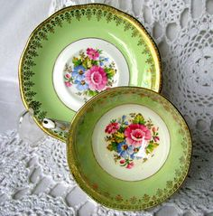 Queen Anne Pink Rose Flower Bouquet Wide Mouth Light Green Teacup and Saucer Circa 1950s early Queen Anne vintage green tea cup set Beautiful pink peony / rose spray in bowl of cup, exterior of cup and center of saucer Gold scrollwork borders on both cup and saucer Plentiful gold on scalloped rim edges, foot of cup and handle of cup Queen Anne Pattern #4749 Bone china Made in England Very good condition - no chips, no cracks. There are a couple of very tiny glaze paint specks from the fa...