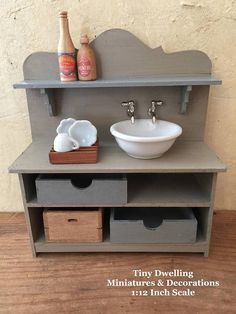 Miniature Sink Lovely dry sink with removable porcelain round sink basin and drawers/storage containers. Very versatile, use in Kitchen or Bathroom. 1:12th scale Ready To Ship. Featured in colors in the following combinations: Gray (Entire Unit) Slate (Shelf) Slate (Two (2) Pullout Drawers) Stain (One (1) Pullout Crate) Ready To Ship, as shown. Features: Handmade/Finished. All Wood Construction. Vintage Porcelain Sink Basin. Paint. Metal Hardware. Three (3) Removable Drawe...