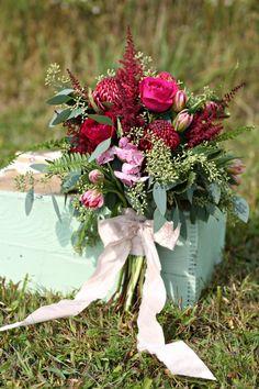 wedding centerpiece burgundy - Google Search waratah protea, 'Darcey' garden roses, burgundy astilbe, pink double tulips, seeded eucalyptus and sword fern