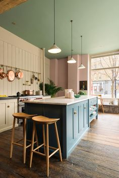 """Two deVOL Bum Stools stand at the end of the kitchen island. The worktop is a large slab of honed Carrara marble. The ceiling is painted in """"Breakfast Room Green"""" by Farrow & Ball. deVOL's Kitchen Showroom in Clerkenwell, London Country Style Kitchen, Beautiful Kitchens, Kitchen Colors, Kitchen Decor, Interior Design Kitchen, New Kitchen, Green Kitchen, Kitchen Showroom, Kitchen Design"""