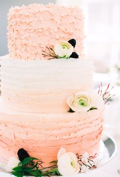 Brides: A three-tiered white-and-pink ruffled cake with sugar flowers. A three-tiered white-and-pink wedding cake with ruffled layers and a top-tier covered in sugar flowers, created by Sugarlips Cakes.