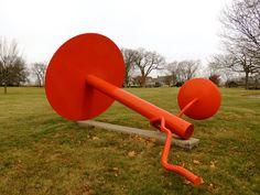 Axeltree. 1967. Aço pintado. Alexander Liberman (Kiev, Ucrânia, 04/09/1912 - 19/11/1999, Miami, Flórida, USA). Encontra-se no Jardim de Esculturas Lynden em Milwaukee, Wisconsin, USA. A escultura é composta por dois discos pintados de vermelho-laranja e ligados por hastes em seus centros. Suas dimensões são 280 cm x 210 cm × 370 cm.  Fotografia: Gabrielle DuCharme no Flickr.