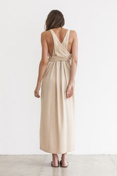 Shaina Mote signature versatile draped dress in an opaque sandy hue. Side straps can be tied around the waist in front or back or twisted around the waistline for different looks. Fits true to size. 1