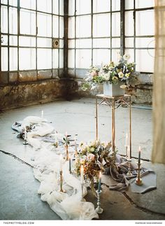 Candle sticks randomly placed alongside swathes of light fabric, together with flowers in muted tones, created a romantic ambience at a St Petersburg mansion. | Photographer: Vivid Symphony | Florist and Décor Supplier: Voulez Vous