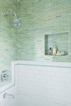 an interesting mix of subway tile, glass mosaics, and tile chair rail trim at the bath